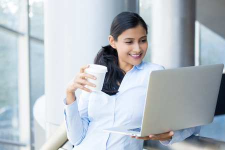 Closeup portrait, young, attractive woman standing, drinking coffee, smiling looking, surfing the silver laptop. Isolated glass window indoor office background. Women in world of technology concept Stockfoto