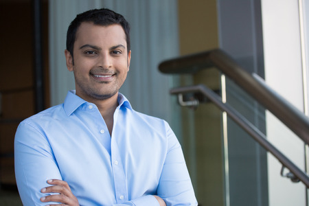 Closeup headshot portrait, happy handsome business man, smiling, arms crossed in blue shirt,confident and friendly on isolated office interior background. Corporate success Stockfoto