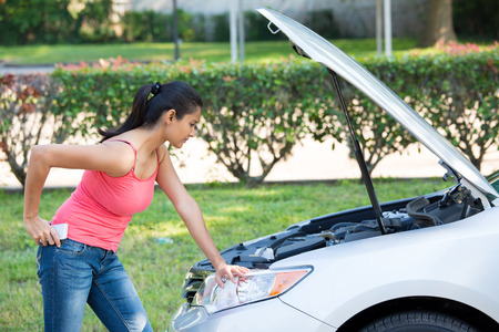 Closeup portrait, young woman in pink tanktop having trouble with her broken car, opening hood and looking at engine to see whats wrong, isolated green trees and shrubs outside background Stock Photo