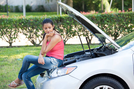 hood: Closeup portrait, young woman in pink tanktop having trouble with her broken car, sitting on open hood engine worried, isolated green trees and shrubs outside background Stock Photo
