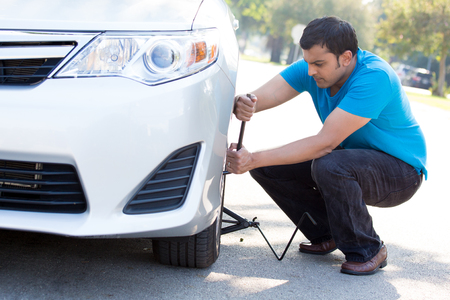 flat tire: Closeup portrait, young man in blue shirt and black jeans happily fixing flat tire with jack and tire iron, isolated green trees and road outside background. Roadside assistance concept Stock Photo