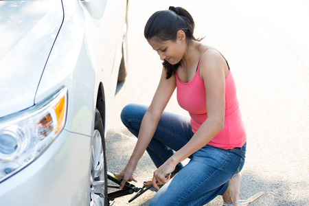roadside assistance: Closeup portrait, young woman in pink tanktop and blue jeans fixing flat tire with jack and tire iron, isolated green trees and road outside background. Roadside assistance concept