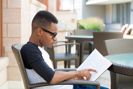 Closeup portrait, smart young nerdy man with big black glasses, sitting down and reading, isolated outdoors background. knowledge is power concept  Stock Photo