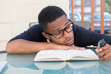 tired worker: Closeup portrait, nerdy young man in big black glasses holding watch, falling very tired of reading, isolated outdoors outside background. The clock is ticking, cant focus