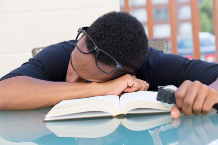 somnolent: Closeup portrait, nerdy young man in big black glasses holding watch, falling very tired of reading, fast asleep, isolated outdoors outside background. Cramming for all-nighter