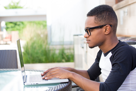 Closeup portrait, young nerdy man in big black glasses surfing the web on personal silver laptop, isolated outside outdoors background