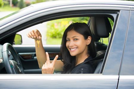 Close-up portret, jonge vrolijke, blije, lachende, prachtige vrouw die sleutels van haar eerste nieuwe auto en vrede of twee teken. Klanttevredenheid Stockfoto