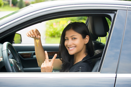 indian money: Closeup portrait, young cheerful, joyful, smiling, gorgeous woman holding up keys to her first new car and peace or two sign. Customer satisfaction