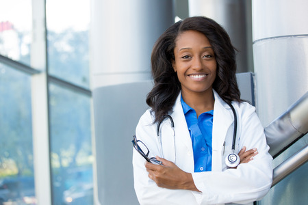 office visit: Closeup headshot portrait of friendly, smiling confident female healthcare professional with lab coat, arms crossed holding glasses. Isolated hospital clinic background. Time for an office visit Stock Photo