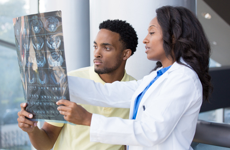 radiographic: Closeup portrait of intellectual healthcare professionals with white labcoat, looking at full body x-ray radiographic image, ct scan, mri, isolated hospital clinic background. Radiology department