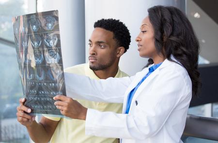Retrato de detalle de los profesionales de la salud intelectual con bata blanca, mirando a la imagen radiográfica del cuerpo radiografía completa, Tomografía computarizada, resonancia magnética, fondo aislado clínica hospital. Departamento de Radiología Foto de archivo - 34973327