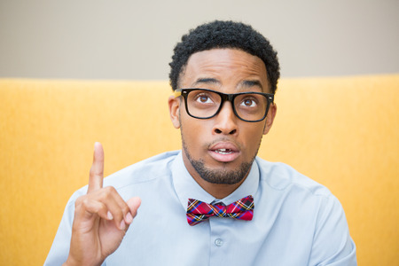choose university: Closeup portrait young man with big black glasses blue shirt and bow tie has an idea, pointing with finger up looking up, isolated yellow gray background. Stock Photo