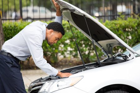 Closeup portrait, young man having trouble with his broken auto, opening hood trying to fix engine, isolated green trees outside background. Car won't start, dead battery Stockfoto