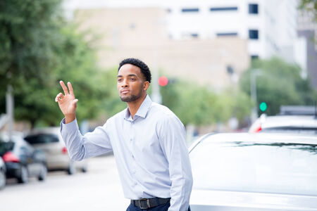 Closeup portrait, young man in blue shirt , raising hand to say hi, goodbye or hitchhike, flag or hail a cab, isolated road and cars background outdoors. Bon voyage