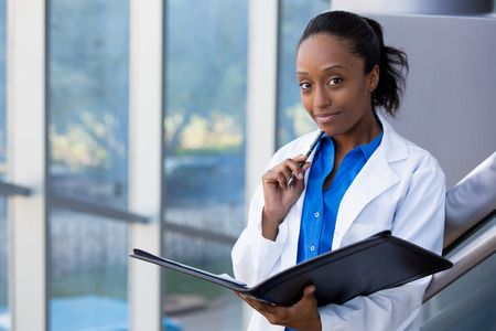 female face: Closeup headshot portrait of friendly, smiling confident female doctor, healthcare professional with labcoat, holding pen to face and holding notebook pad. Isolated hospital clinic background.