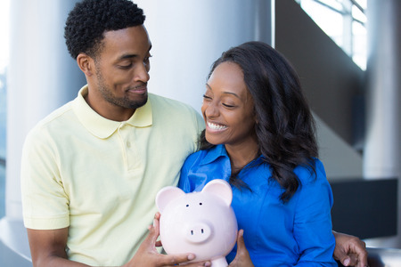 black business man: Closeup portrait, happy handsome couple or two business people holding pink piggy bank looking at each other, laughing.  Smart financial decisions