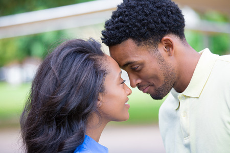 Closeup portrait of a young couple, guy in yellow shirt looking into womans eyes with blue shirt, head to head, happy moments, positive human emotions, isolated outside outdoors background