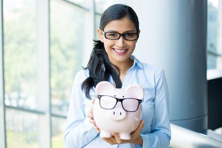Close-up portret gelukkig, lachend zakelijke vrouw, die roze spaarvarken, het dragen van grote zwarte bril geïsoleerd binnen kantoor achtergrond. Financiële besparingen op de begroting, slimme investering begrip