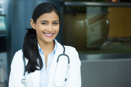 Closeup portrait of friendly, smiling confident female doctor, healthcare professional with labcoat and stethoscope, isolated indoors clinic hospital background