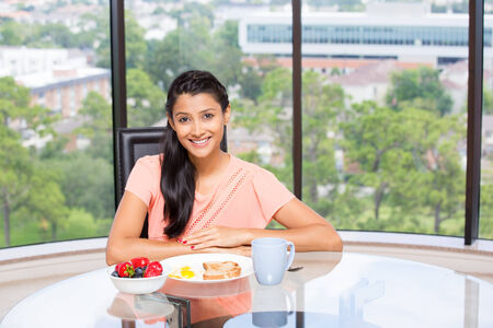 dietitian: Closeup portrait of a young, attractive businesswoman, kick start day with healthy breakfast, fruit bowl, egg ,green tea, smiling energetic employee. Isolated glass window indoor greenery background.