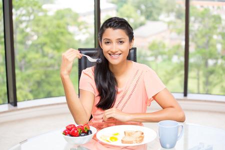 fille arabe: Portrait Gros plan d'un jeune, femme d'affaires attrayant, Kick Start journée avec petit déjeuner sain, bol de fruits, oeufs, thé vert, sourire employé énergique. Fenêtre en verre isolée verdure intérieure arrière-plan. Banque d'images