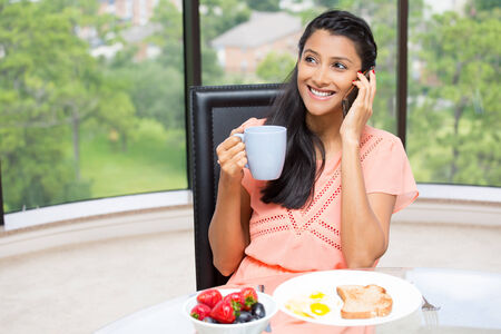 Closeup portrait of a young, attractive businesswoman, kick start day, health breakfast, fruit bowl, egg ,green tea, smiling, talking over the phone. Isolated glass window indoor greenery background. photo
