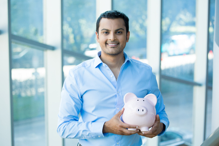 college fund savings: Closeup portrait happy, smiling businessman, holding pink piggy bank, isolated indoors office background. Financial budget savings, smart investment concept Stock Photo