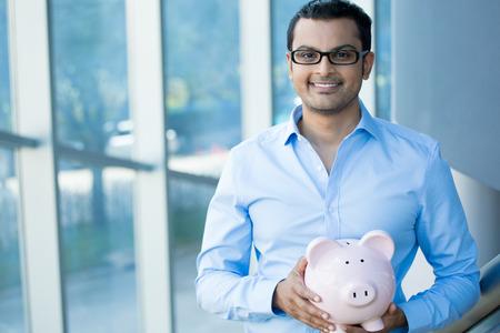 Close-up portret gelukkig, lachend zakenman, die roze spaarvarken, geïsoleerd binnen kantoor achtergrond. Financiële besparingen op de begroting, slimme investering begrip
