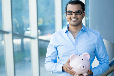 education loan: Closeup portrait happy, smiling businessman, holding pink piggy bank, isolated indoors office background. Financial budget savings, smart investment concept Stock Photo