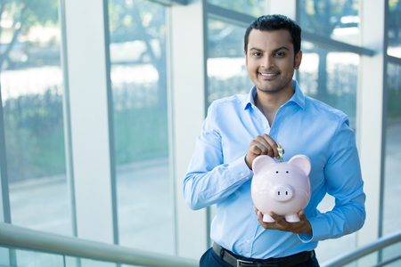 mutual funds: Closeup portrait happy, smiling businessman, placing money in pink piggy bank, isolated indoors office background. Financial budget savings, smart investment concept