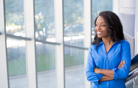 Primer retrato, joven profesional mujer hermosa, confía en camisa azul, personalidad amable, sonriente, mirando la ventana de vidrio exterior, en el interior aisladas oficina fondo. Emociones humanas positivas