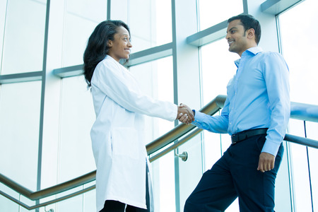 Closeup portrait of health care professional or doctor or nurse shaking hands with patient, indoors clinic hospital background Banque d'images