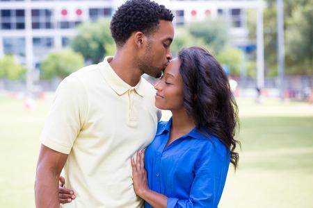 若いカップルのクローズ アップの肖像画、男女性とキス顔、幸せな瞬間、肯定的な人間の感情を保持分離屋外外パーク背景。