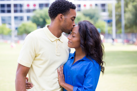 Closeup portrait of a young couple, guy holding woman and kissing face, happy moments, positive human emotions on isolated outdoors outside park background.