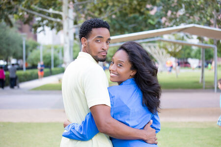 hitched: Closeup portrait of a young couple holding, embracing each other, expression of love, happy moments, positive human emotions on isolated outdoors park background. Woman and man looking back