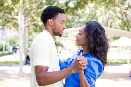 Closeup portrait of a young couple, guy holding woman in arms, looking at each other, dance pose, love and romance concept, positive human emotions on isolated outdoors outside park background.
