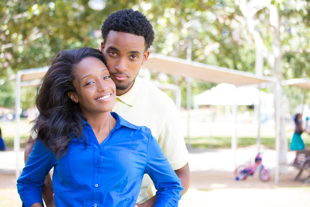 Closeup portrait of a young couple, guy in yellow shirt holding woman with blue shirt from behind, happy moments, positive human emotions on isolated outdoors outside background. Editorial