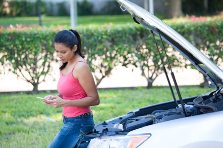 Closeup portrait, young woman in pink tanktop having trouble with her broken car, opening hood and texting for help on cell phone, isolated green trees and shrubs outside background
