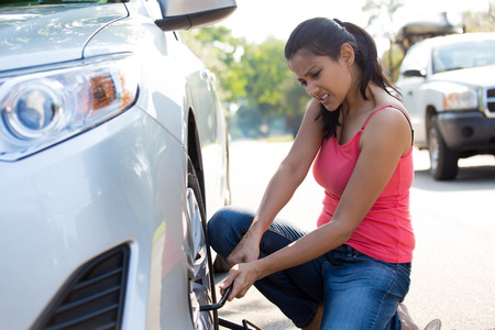 Closeup portrait, young woman in pink tanktop and blue jeans fixing flat tire with jack and tire iron, isolated green trees and road outside background. Roadside assistance concept