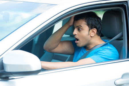 buy car: Closeup portrait, dumbstruck, dumbfounded young sitting man in blue shirt, wide open eyes and mouth by drivers in front of him, isolated city street background. Outrageous driving accident events.