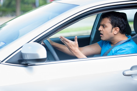 Closeup portrait, angry young sitting man pissed off by drivers in front of him and gesturing with hands, isolated city street background. Road rage traffic jam concept.