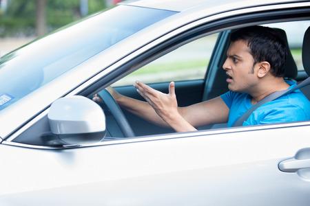 Portrait Gros plan, jeune homme en colère salon énervé par les conducteurs en face de lui et gestes avec les mains, ville isolée rue arrière-plan. la rage au concept de la confiture de la circulation routière.