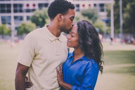 若いカップルのクローズ アップの肖像画、男女性とキス顔、幸せな瞬間、肯定的な人間の感情を保持分離屋外外パーク背景。レトロなビンテージの
