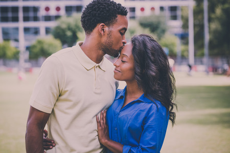 Closeup portrait of a young couple, guy holding woman and kissing face, happy moments, positive human emotions on isolated outdoors outside park background. Retro aged vintage  look
