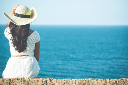 looking at: Closeup back view of woman sitting in white dress and hat looking out towards blue ocean and sky, isolated sea background