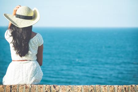 mujer mirando el horizonte: Vista posterior del primer de la mujer sentada en vestido blanco y sombrero mirando hacia el océano y el cielo azul, aislado en fondo del mar Foto de archivo