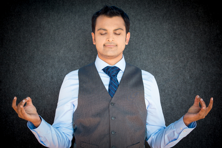 isolated on gray: Closeup portrait of handsome, young man in vest and tie in meditation zen mode, isolated gray black background. Stress relief techniques concept.