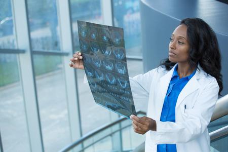 Close-up portret van de intellectuele vrouw medisch personeel met witte labjas, kijkend naar de foto lichaam x-ray radiografie, CT-scan, MRI, geïsoleerde ziekenhuis kliniek achtergrond. Afdeling radiologie