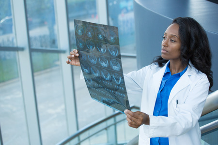 medical doctors: Closeup portrait of intellectual woman healthcare personnel with white labcoat, looking at full body x-ray radiographic image, ct scan, mri, isolated hospital clinic background. Radiology department