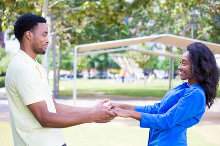Closeup portrait, young couple, guy in yellow shirt looking into woman eyes with blue shirt, face to face, holding hands, happy moments, positive human emotions, isolated outside outdoors background photo